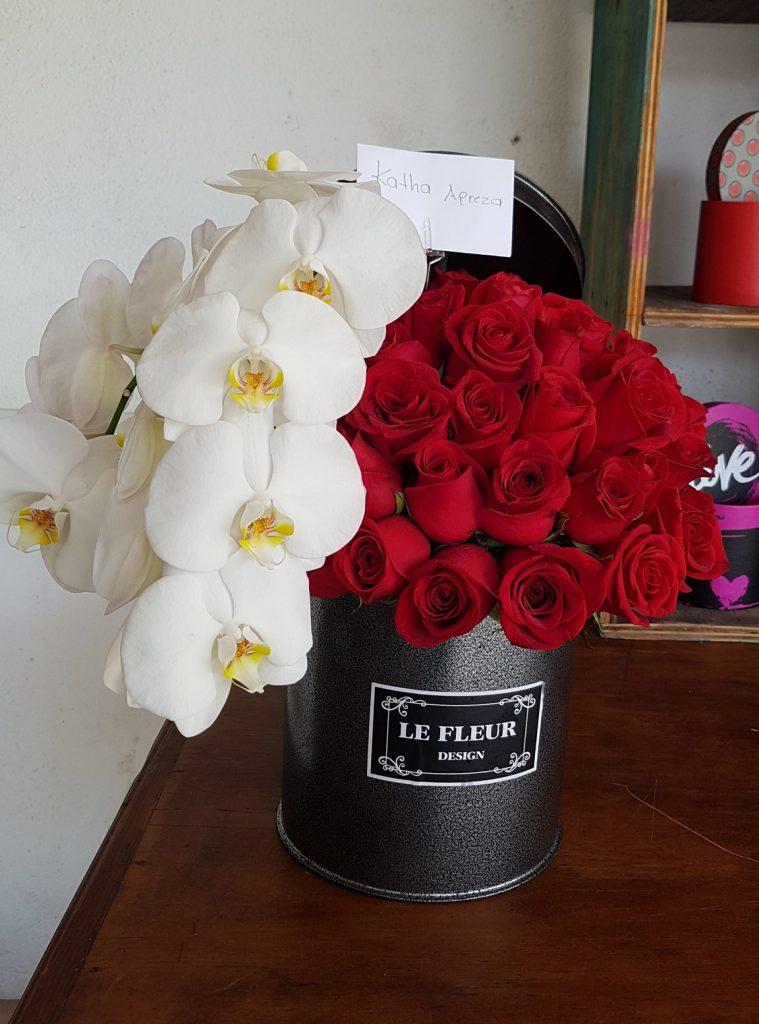 Caja negra con rosas rojas y orquídeas blancas